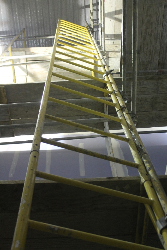 A ladder leads the eye up in a scaffolded stairwell.