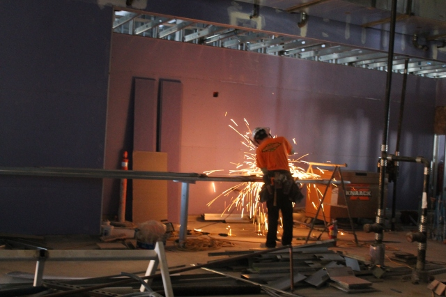 A crew member cuts metal framing in the cafe area.