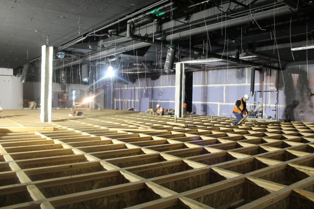 Crew members lay out the gridwork that will support the wooden flooring in Aztec Lanes.