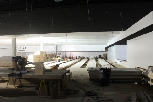 Crew members install the wood flooring in Aztec Lanes.