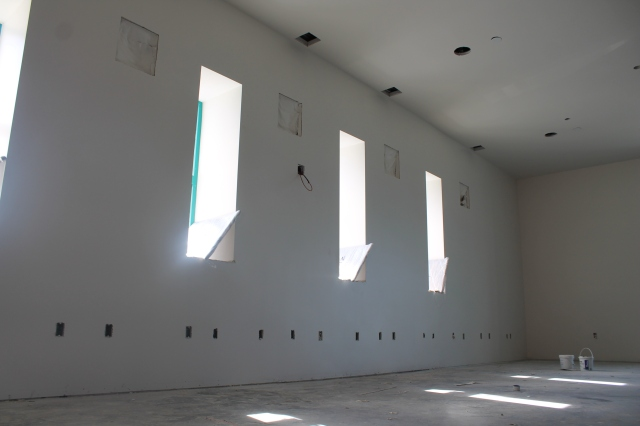 Large-screen TVs will be placed between each vertical window on the east-facing wall.