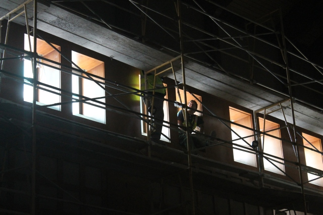 Crew members take a moment to chat while working on the high windows in the theater.